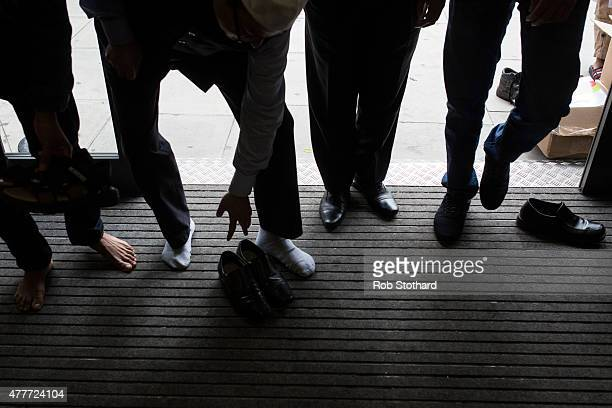 Men remove their shoes upon entering the East London Mosque to attend first Friday prayers of the Islamic holy month of Ramadan on June 19 2015 in...