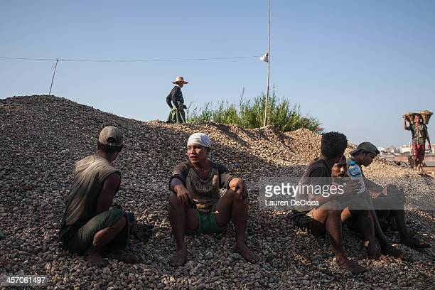 Men rest from recycling oil in a gravel pit on the banks of the Irrawaddy River on December 16 2013 in Yangon Myanmar Large cargo ships on the...