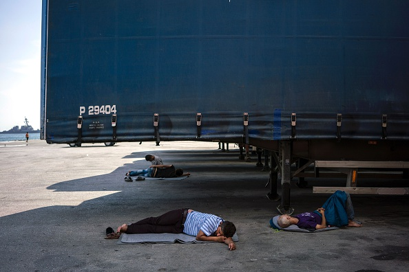 Men rest on the ground next to trucks parked at the port of Piraeus, where nearly 1,500 refugees and migrants live at a makeshift camp or in passenger areas, in Athens on July 3, 2016