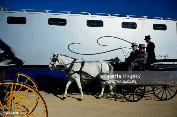 Men ride a horse carriage before an exhibition at the Sicab 2017 International Horse fair in Sevilla on November 16 2017 / AFP PHOTO / CRISTINA...