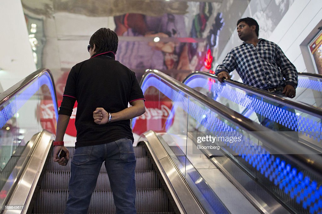 Men ride an escalator at the AlphaOne shopping mall in Amritsar, India, on Thursday, May 9, 2013. India's consumer price index (CPI) for April rose 9.39 percent year on year, the Central Statistics Office said in a statement on its website. Photographer: Brent Lewin/Bloomberg via Getty Images