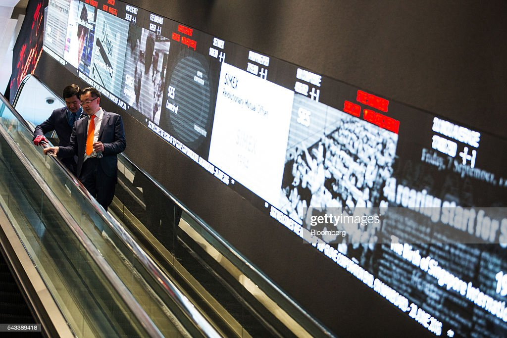 Men ride an escalator past an electronic screen at the Singapore Exchange Ltd. (SGX) headquarters in Singapore, on Tuesday, June 28, 2016. Days after the surprise U.K. vote for Brexit started roiling global markets, prospects for greater monetary and fiscal stimulus are becoming clear in Asia, even as the region's relative growth dynamism offers it resilience. Photographer: Nicky Loh/Bloomberg via Getty Images