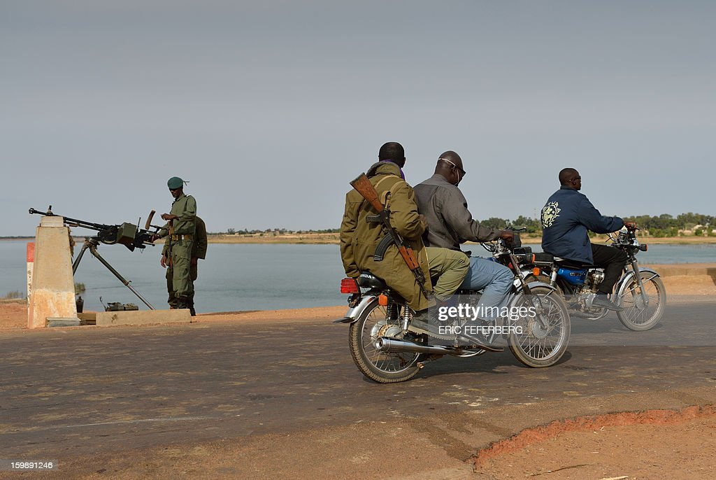 Men ride motorcylces past a Malian soldier holding a machine gun as he stands guard at the entrance of a strategic bridge over the Niger river on January 22, 2013, near Markala, some 270km north of Bamako. Mali's army chief today said his French-backed forces could reclaim the northern towns of Gao and fabled Timbuktu from Islamists in a month, as the United States began airlifting French troops to Mali.