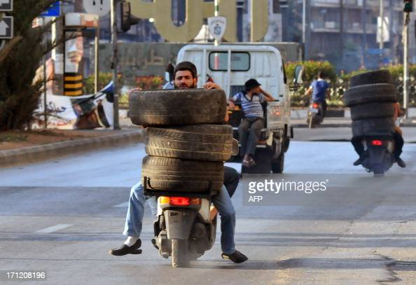 Men ride on mopeds as they transport tires towards a burning barricade in the northern city of Tripoli on June 23 during protests in support of Sunni...