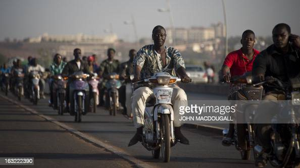 Men ride their motorbikes on a bridge over the river Niger in Bamako on March 6 2013 AFP PHOTO / JOHN MACDOUGALL