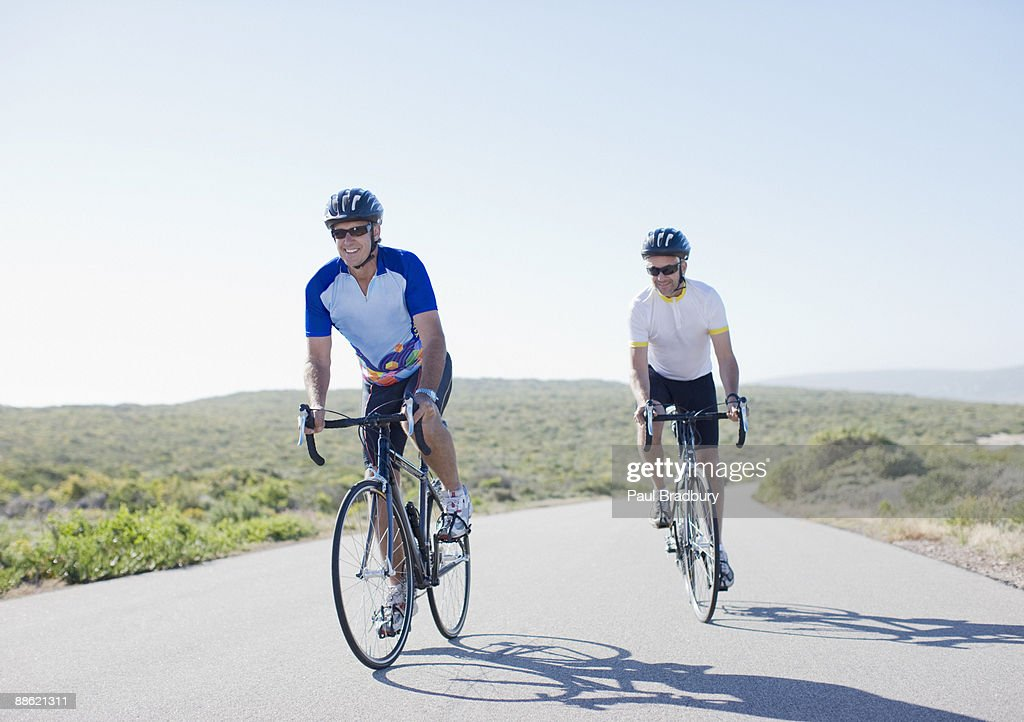 Men riding bicycles on remote road : Stock Photo