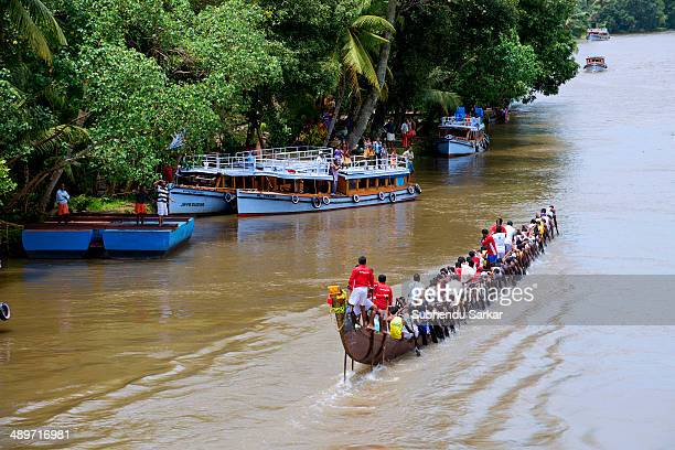 Men row a snake boat during Paipad Boat race