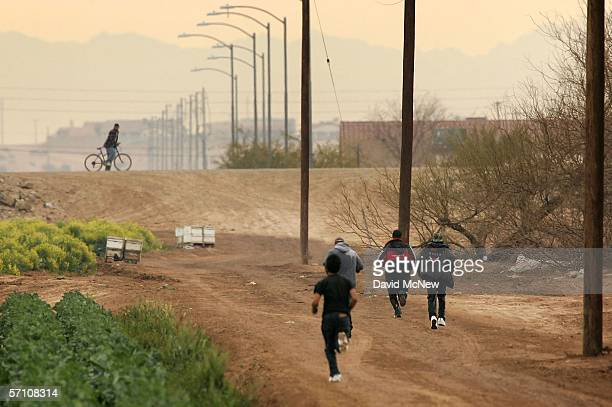 Men run after crossing illegally into the US from Mexico on March 16 2006 at the border town of near San Luis south of Yuma Arizona As Congress...