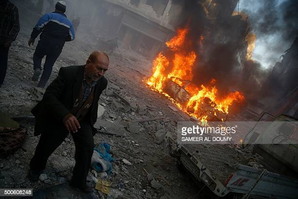 Men run past debris and a burning car following reported airstrikes on the town of Hamouria in the eastern Ghouta region a rebel stronghold east of...