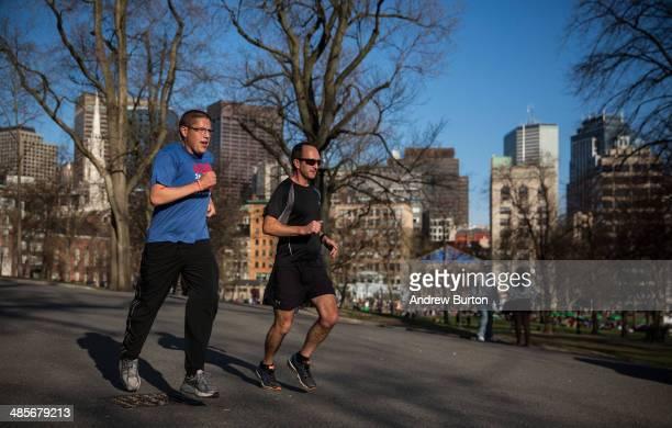 Men run through Boston Common two days before the Boston Marathon on April 19 2014 in Boston Massachusetts This year's marathon will be held on...