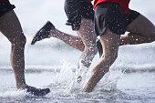 Men running in ocean, low section