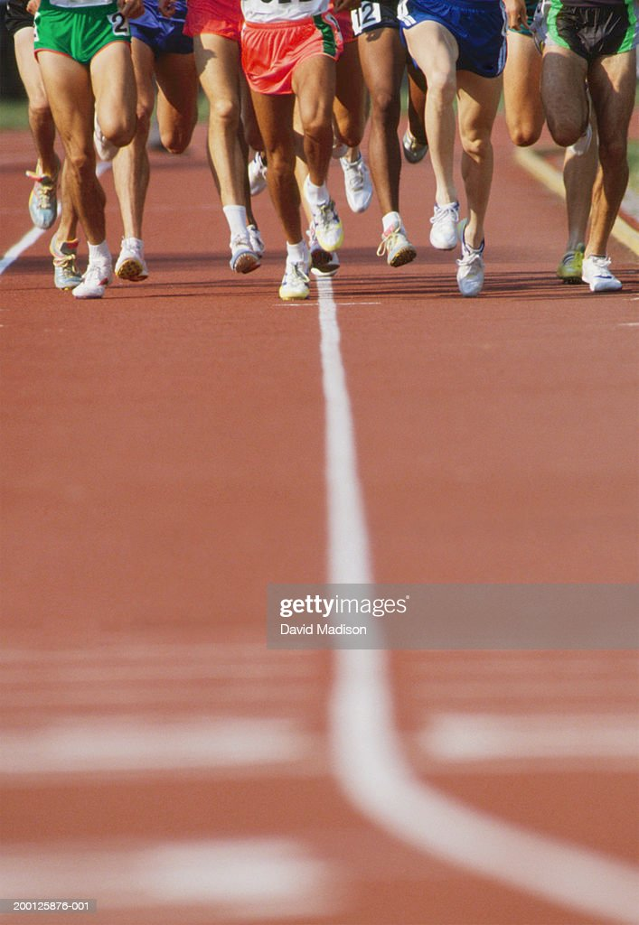 Men running in track and field distance race, low section : Stock Photo