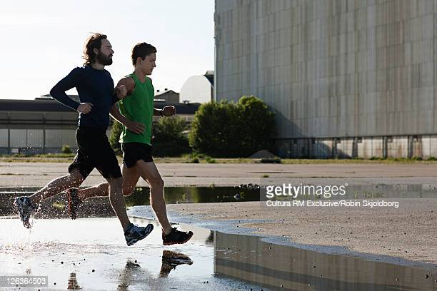 Men running on puddles in concrete