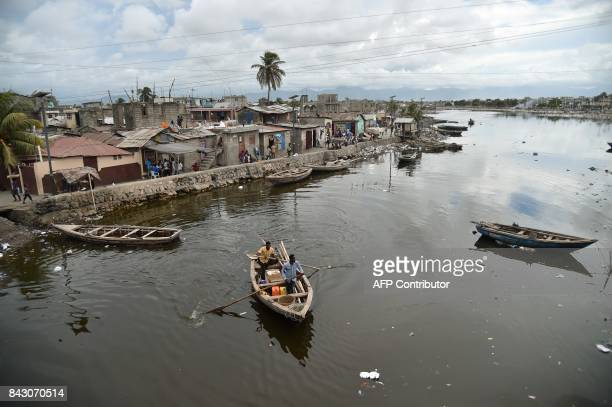 TOPSHOT Men sail on Mapou River in Mapou River in CapHaitien in the north of Haiti 240 km from PortauPrince ahead of Hurricane Irma on September 5...