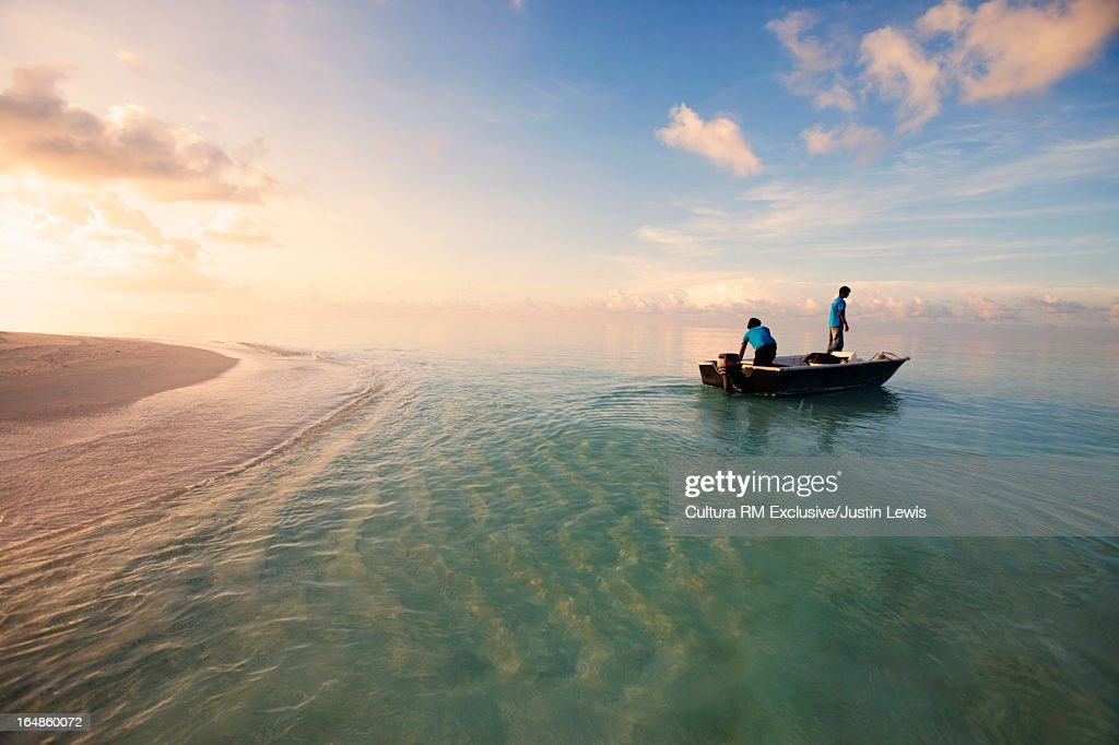 Men sailing in boat in tropical water