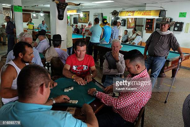 Men sat at a table in agames hall play a game of Domino while in the background others are busy at Pool tables on a Sunday in the main town square on...