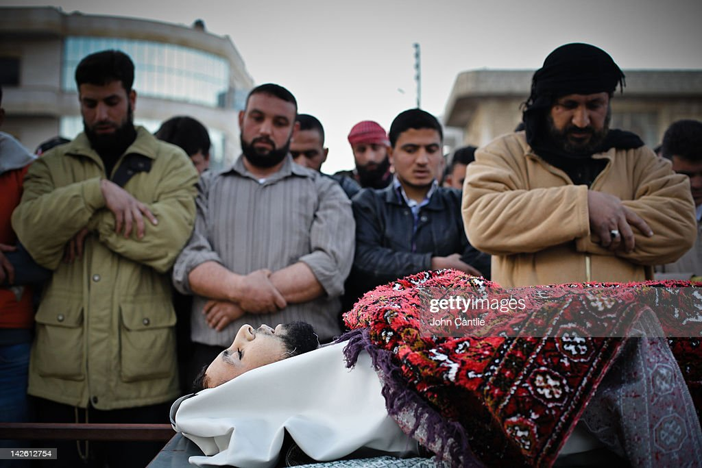 Men say prayers near the body of a man killed during clashes with government forces, during a ceremony in Binnish on April 9, 2012 in Binnish, Syria. Conitnuing violence in northern Syria between government forces and rebels is putting plans for a UN-brokered Syria ceasefire on Tuesday in jeopardy.