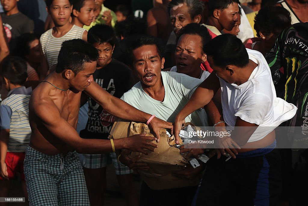 Men scramble for supplies after an air drop by the Philippine Air Force at first light in a remote village on November 16 2013 in Leyte Philippines...