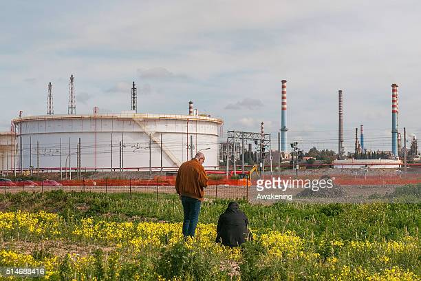 Men search for damages near the oil refinery in the center of the city on March 10 2016 in Taranto Apulia Italy A national referendum on oil drilling...