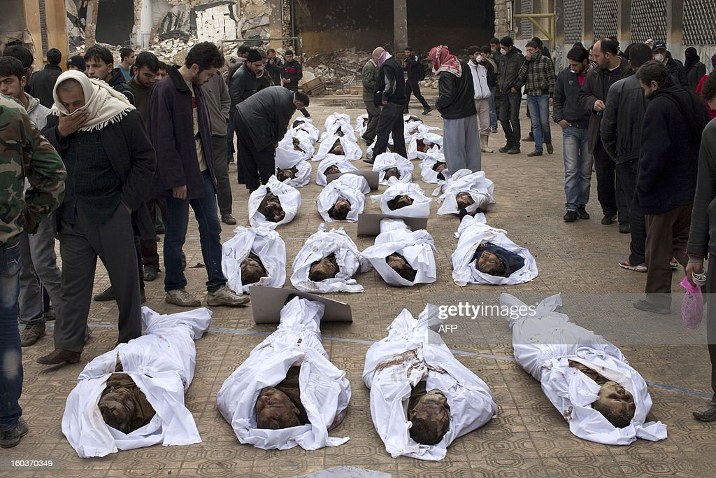 Men search for their relatives amongst the bodies of Syrian civilians executed and dumped in the Quweiq river, in the grounds of the courtyard of the Yarmouk School, in the Bustan al-Qasr district of Aleppo on January 30, 2013. Syria's opposition charged that 'global inaction' was giving Bashar al-Assad's regime a license to kill, a day after dozens of young men were found shot execution-style in the city of Aleppo.