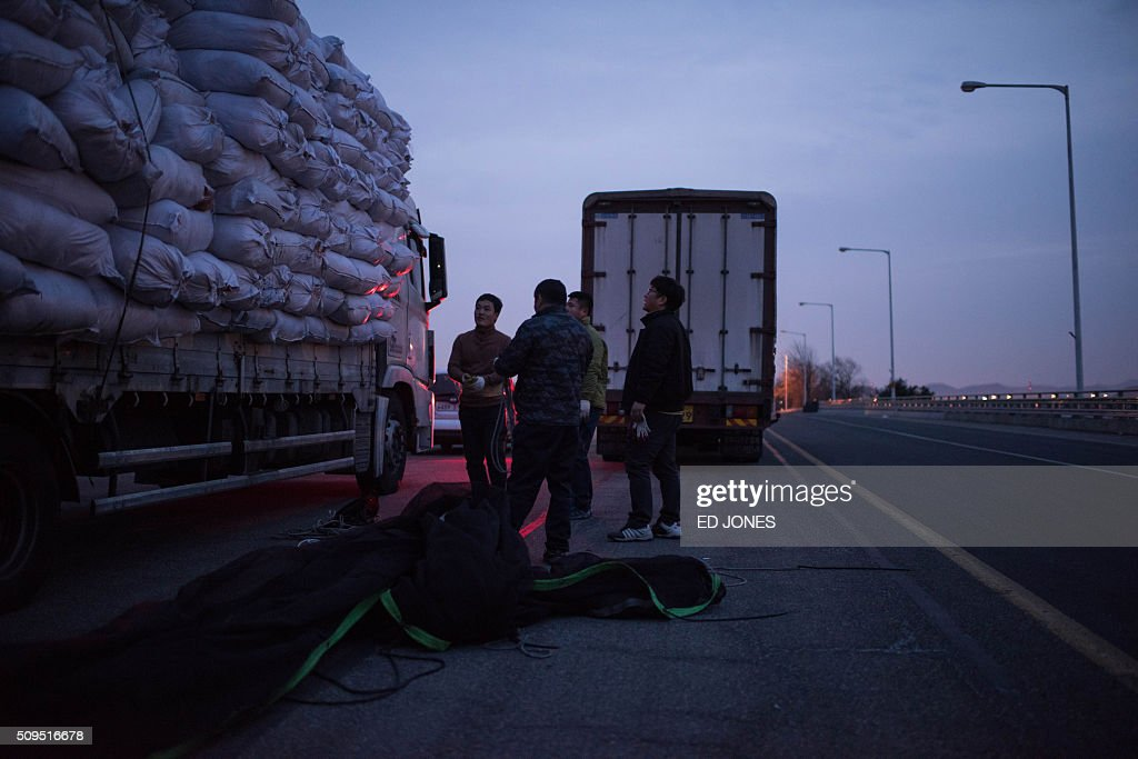 Men secure the cargo of a vehicle which arrived from the Kaesong joint industrial zone, on a roadside outside a checkpoint near the Demilitarized Zone (DMZ) separating the two Koreas in Paju on February 11, 2016. North Korea on February 11 expelled all South Koreans from the jointly-run Kaesong industrial zone and seized their factory assets, saying Seoul's earlier decision to shutter the complex had amounted to a 'declaration of war'. AFP PHOTO / Ed Jones / AFP / ED JONES