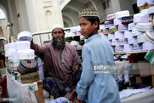 Men sell taqiyah caps outside the National Mosque during EidAlAdha on October 16 2013 in Dhaka Bangladesh Eid AlAdha known as the 'Feast of the...