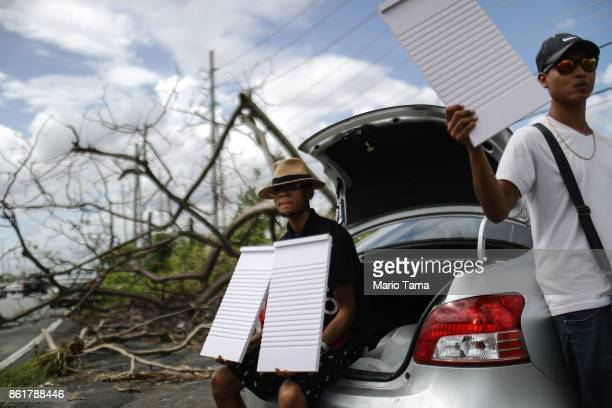 Men sell washing boards from the back of a car on the side of a main road in an area without electricity on October 15 2017 in San Isidro Puerto Rico...