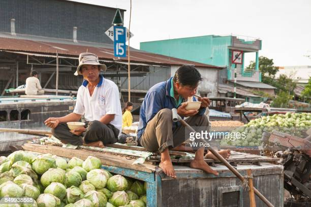 Men selling vegetables from a boat in the floating market Cai Rang near Can Tho Mekong River Delta Vietnam