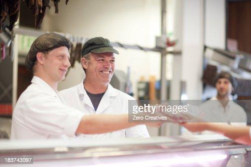 Men serving customer on butcher's counter