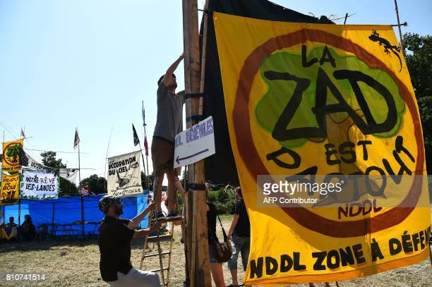 Men set up a bannrer reading 'The ZAD is everywhere NDLL Zone to defend' during a twoday meeting organised by opponents to a controversial...