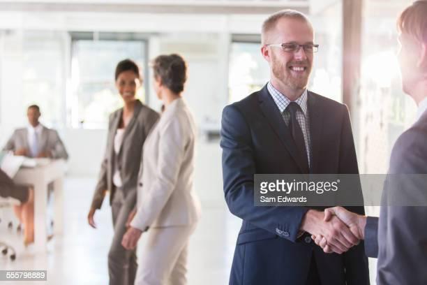 Men shaking hands, colleagues in background