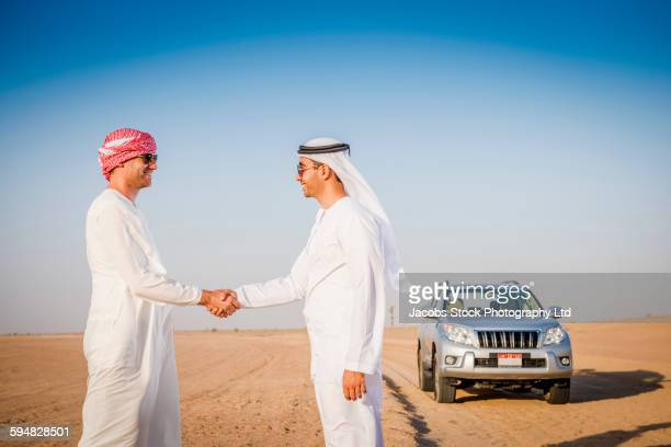 Men shaking hands in desert