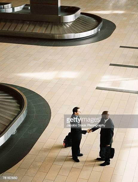 Men shaking hands near baggage claim