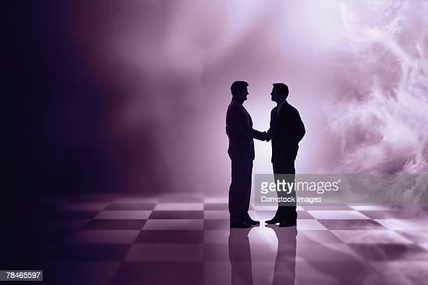 Men shaking hands on a chessboard