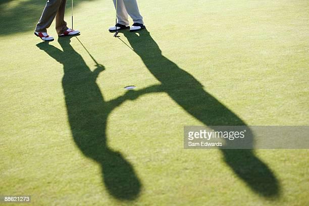 Hommes se serrant la main sur un putting green