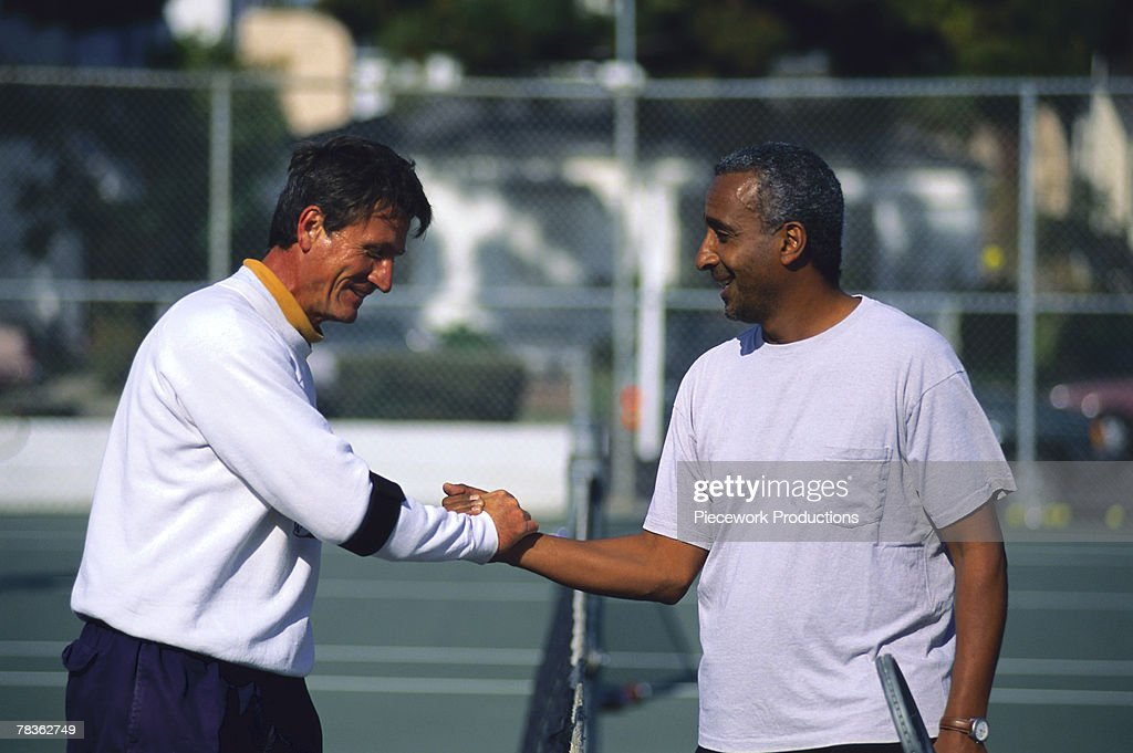 Men shaking hands on tennis court : Stock Photo
