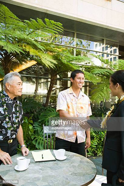 Men shaking hands with businesswoman outdoors