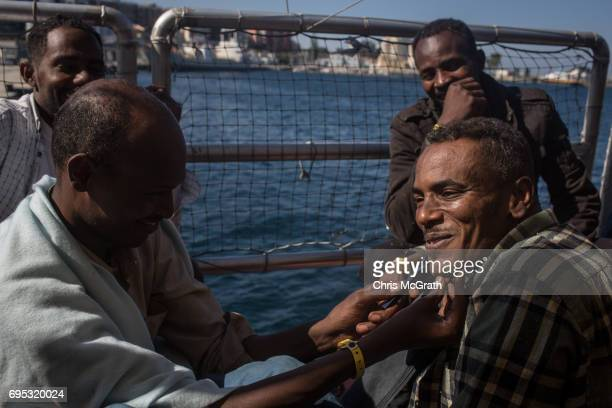 Men shave before disembarking the Migrant Offshore Aid Station Phoenix vessel on June 12 2017 in Reggio Calabria Italy An estimated 230000 refugees...