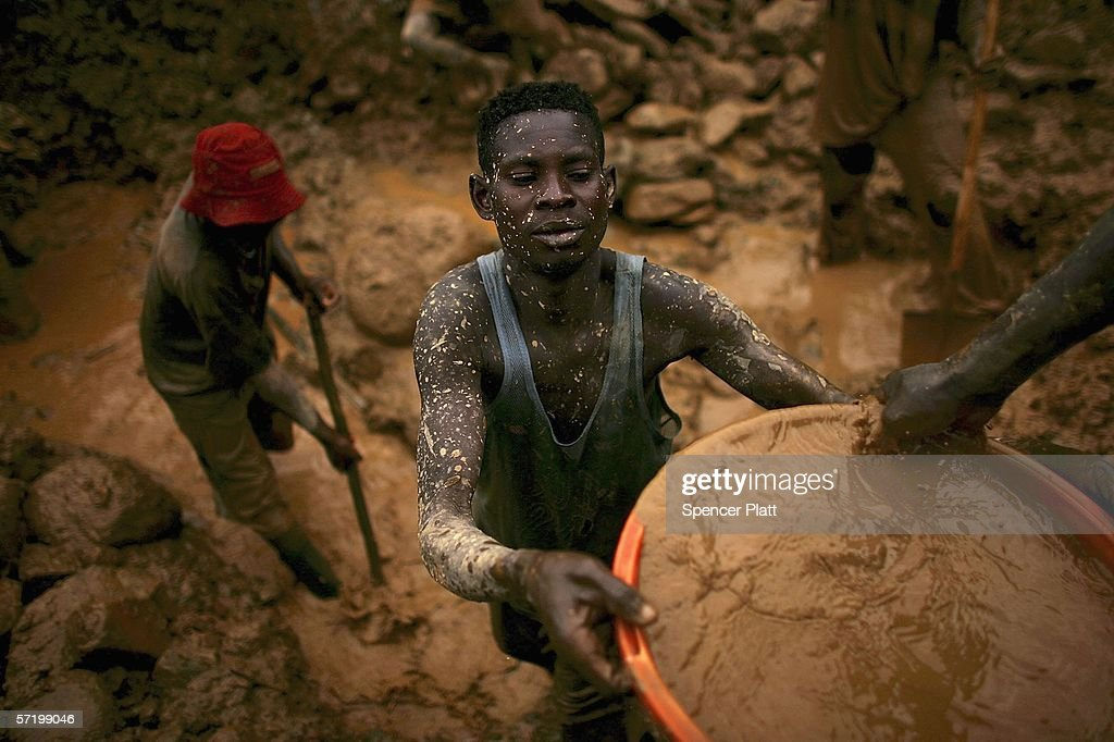 Men sift through buckets of dirt while looking for gold at an abandoned industrial mine March 28 2006 in Mongbwalu Congo Thousands of Congolese...