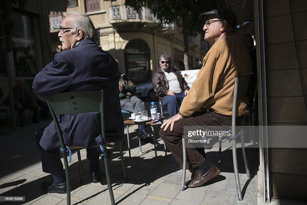 Men sit and watch from the terrace of an outdoor cafe in Nicosia, Cyprus, on Monday, March 25, 2013. In a replay of tensions over aid for Greece at the outset of the crisis, European governments had wrangled over aid for Cyprus for nine months, exposing holes in the revamped economic management system that was built in three years of emergency policymaking, often at all-night summits. Photographer: Photographer: Simon Dawson/Bloomberg via Getty Images