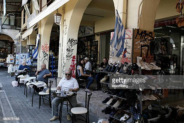 Men sit at outdoor cafe tables near decorative Greek national flags in Thessaloniki Greece on Monday July 13 2015 Greece has been in financial limbo...