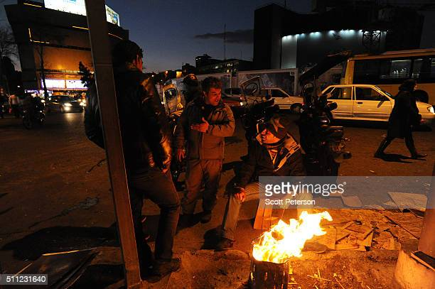 Men sit by a fire in Tehran's central Vali Asr Square beneath a large antiAmerican banner that depicts US Marines raising the flag at Iwo Jima during...