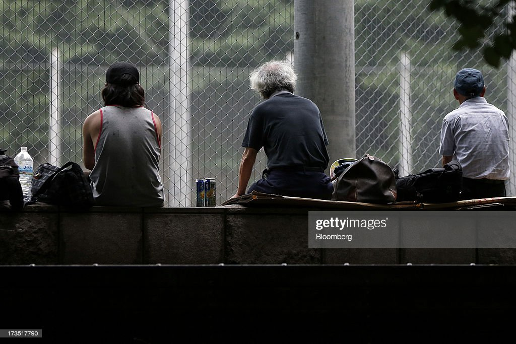 Men sit in a park in Tokyo, Japan, on Monday, July 8, 2013. The number of Japanese seniors living alone will rise 54 percent to 7.17 million in 2030 from 4.66 million in 2010, according to the National Institute of Population and Social Security Research, set up by the Ministry of Health, Labour and Welfare. To manage the costs stemming from the aging society, the government aims to push back the pension age to 65 from 60 in stages through 2025. Photographer: Kiyoshi Ota/Bloomberg via Getty Images
