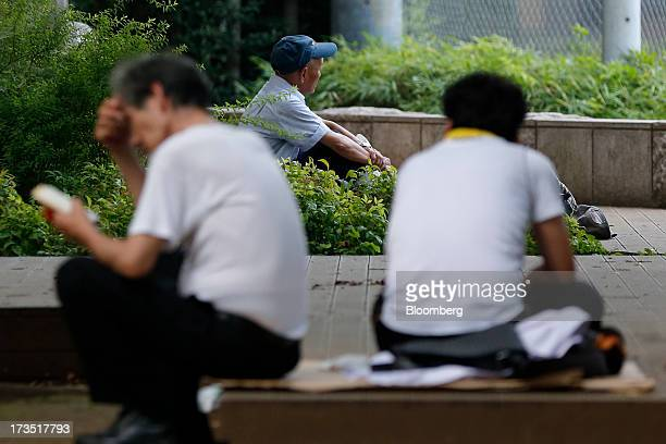 Men sit in a park in Tokyo Japan on Monday July 8 2013 The number of Japanese seniors living alone will rise 54 percent to 717 million in 2030 from...