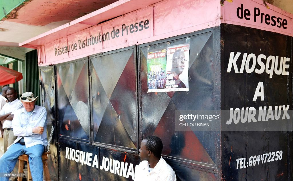 Men sit in front of a closed newspaper stand in Conakry on February 9, 2016, on a 'press-free day' in honour of a journalist who was shot dead last week. Five media associations called for justice and a 'press-free day' on February 9 in honour of journalist El Hadj Mohamed Diallo who died on February 5 after receiving a bullet to the chest in the capital Conakry during clashes outside the offices of an opposition party. / AFP / CELLOU BINANI