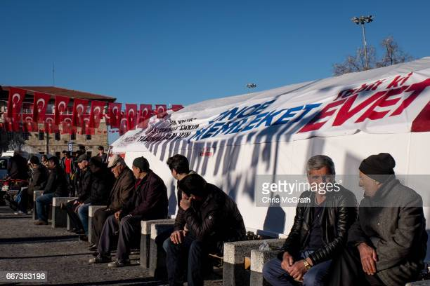 Men sit in front of an Evet campaign tent in the main square on April 11 2017 in Sivas Turkey Campaigning by both the 'Evet' and 'Hayir' camps has...