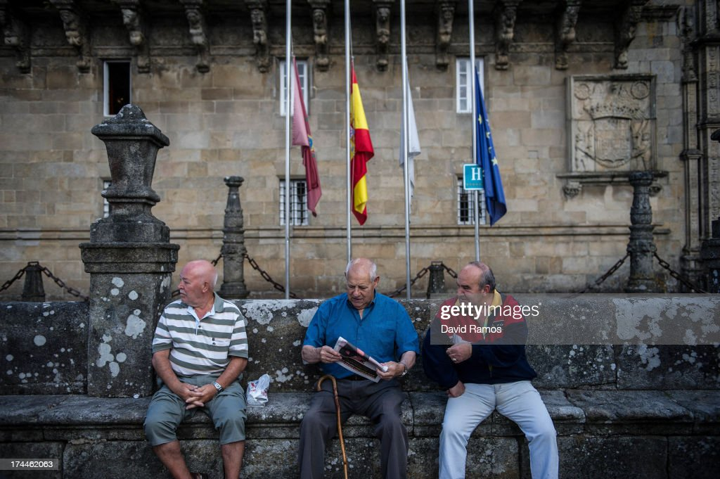 Men sit in Obradoiro square beneath flags flying at half mast in memory of the train crash victims , on July 26, 2013 in Santiago de Compostela, Spain. The high speed train crashed after it derailed on a bend as it approached the north-western Spanish city of Santiago de Compostela at 8.40pm on July 24th. At least 78 people have died and a further 131 are reported injured. The crash occured on the eve of the Santiago de Compostela Festivities.