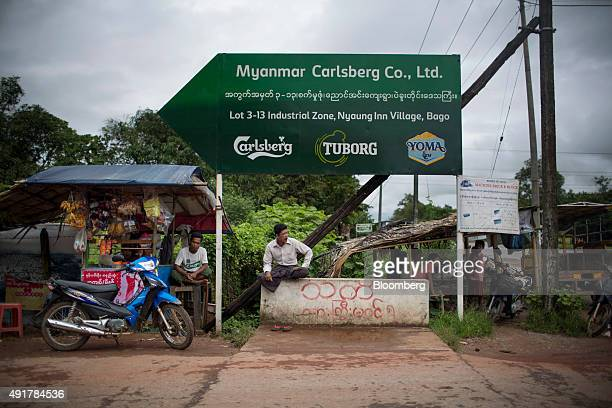 Men sit near a sign for the Myanmar Carlsberg Co plant in Nyaung Inn Village Bago Myanmar on Wednesday Oct 7 2015 Carlsberg opened the $75 million...
