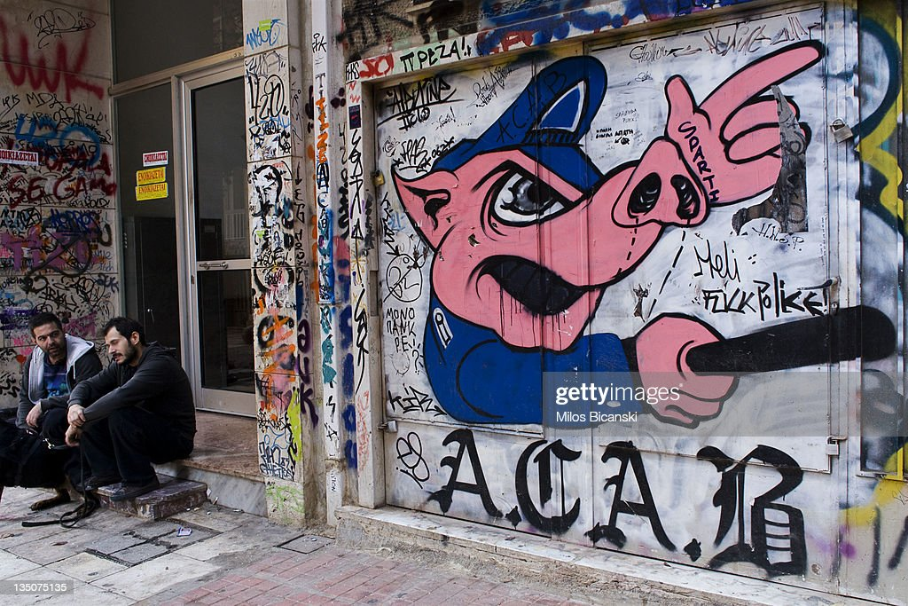 Men sit near graffiti displayed on a building on December 6, 2011 in Athens, Greece. Graffiti artists throughout the city are expressing the effects of austerity measures that have plagued the community as Greece continues to struggle in debt while lawmakers today are set to pass next year's budget.