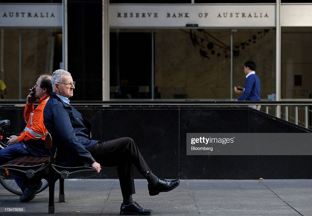 Men sit on a bench outside the Reserve Bank of Australia (RBA) headquarters in the central business district of Sydney, Australia, on Monday, July 15, 2013. While the RBA previously needed higher interest rates to control price pressures as the Australian economy expanded since 1991 without a recession, Governor Glenn Stevens has slashed the cash target, predicting a mining boom will wane. Photographer: Dan Himbrechts/Bloomberg via Getty Images